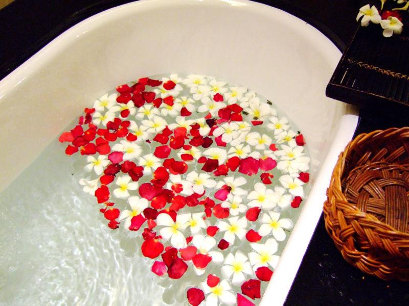 赤や白の花びらが浮かべられたバスタブ