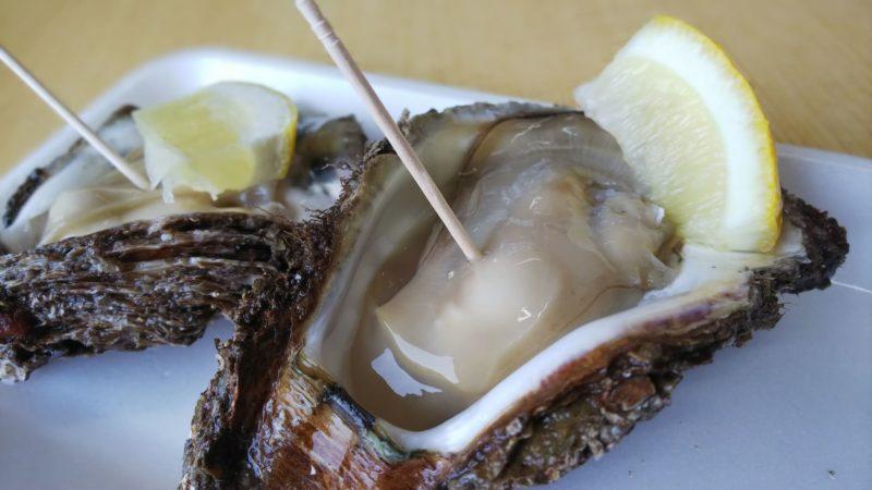 料理され楊枝に差してある牡蠣のつぼ焼き