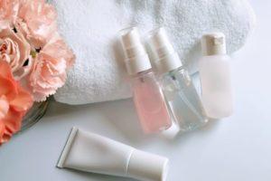 カーネーションとタオルと一緒に置かれている化粧品のミニボトル