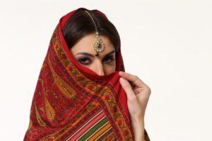 赤いスカーフで顔を隠した中東風な女性
