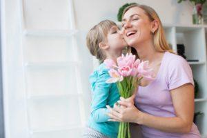 ママに花のプレゼントをしてほっぺにキスをしている女の子