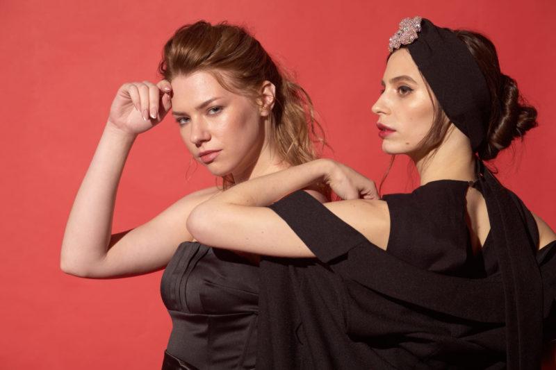 赤い背景で黒い服を着てポーズをとっている彫りの深い女性二人