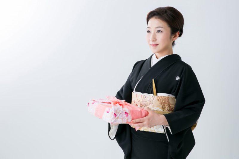 黒い着物を着て供物を届ける日本人女性