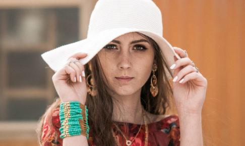 鼻にそばかすができてて白い帽子で隠している女性