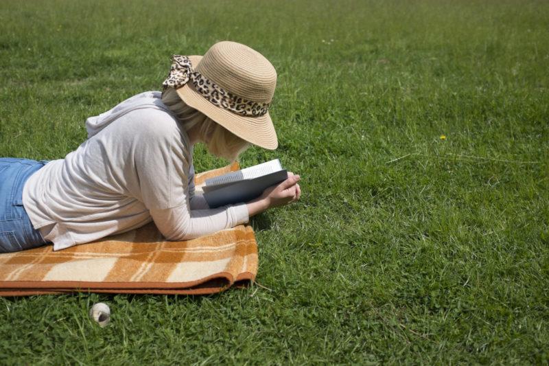 芝生でうつぶせになって本を読んでいるパーカーと帽子の女性
