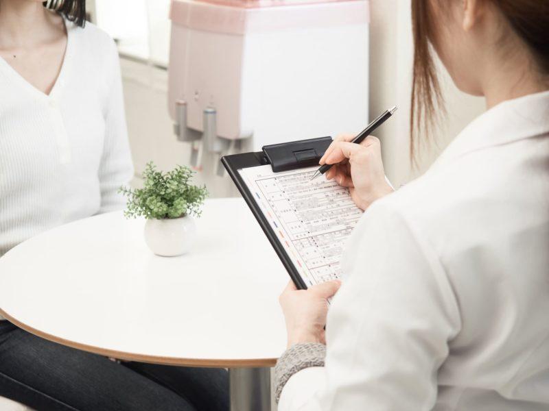問診で女性の患者の話を聞いていく女性看護師