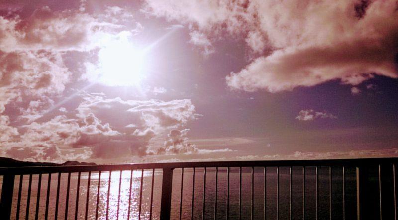 たくさんの雲にセピア色に光が差している海