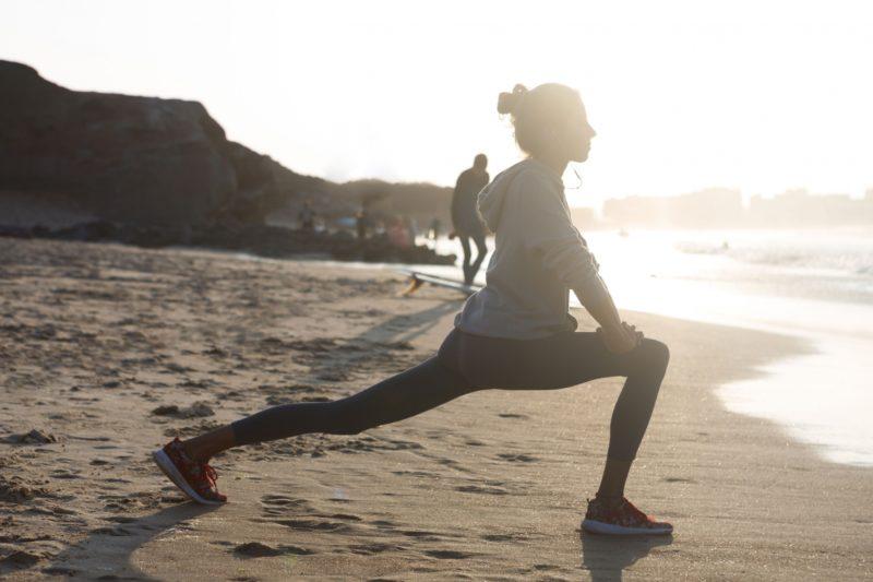 日差しの強い浜辺で運動をする女性