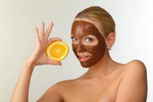 茶色い泥パックをしてオレンジを持ちながらポーズしている女性