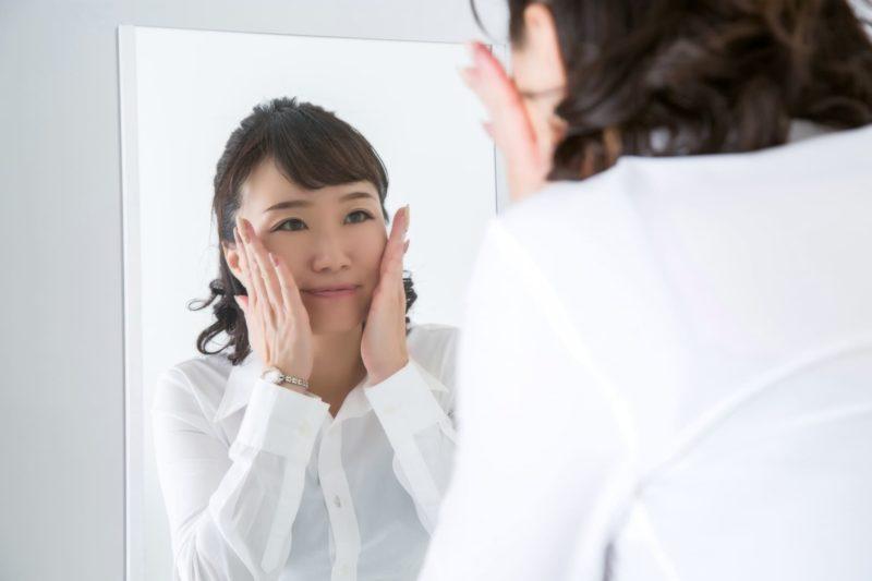 鏡を見て両手を頬に当てる女性