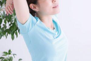 大きく伸びをしている水色Tシャツを着た女性の脇