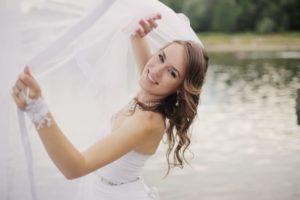 池をバックにウエディングドレス姿の女性
