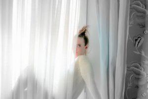 白いカーテンから半分顔をのぞかせている外国人女性