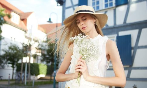 街でカスミソウを持っている帽子の女の子