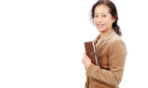 茶色いスーツを着てプレゼンを始めようとしているミセス
