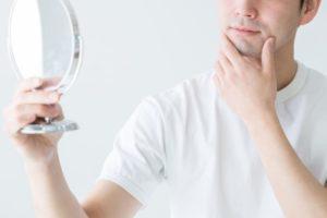 手鏡を気にする成人男性