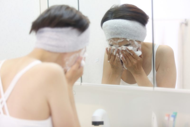 鏡の前でしっかり顔を洗う女性