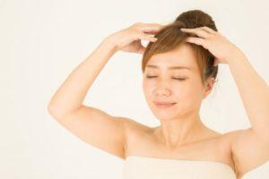 両手で頭皮をマッサージする女性