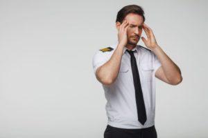 眉間にしわを寄せて頭を抱えている男性パイロット