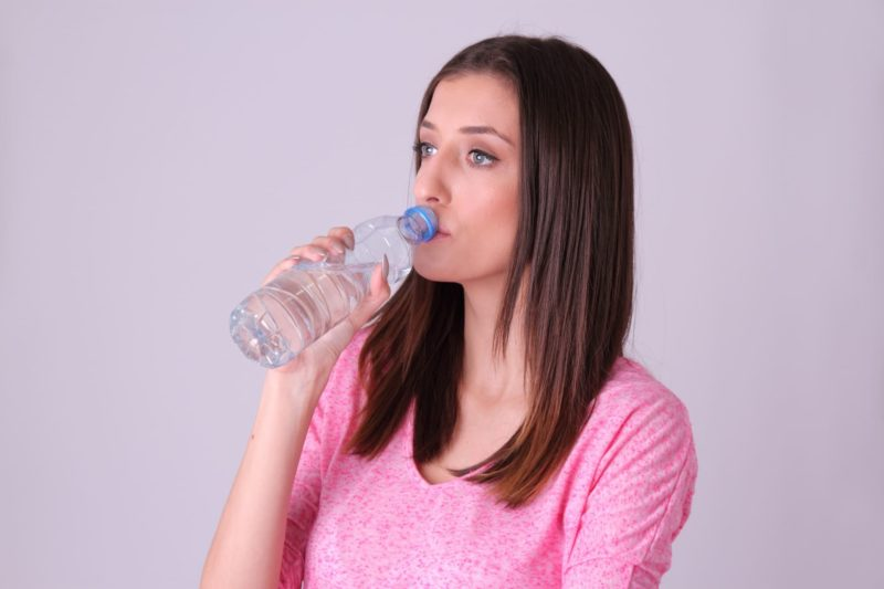 水をごくごく飲んでいるピンクの服着た女性
