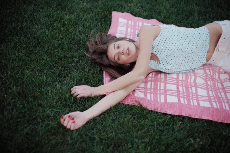 芝生にピンクのシートを敷いてお腹を出している女性