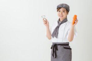 ニンジンとピーラーを持ってるカフェ勤務風の女性