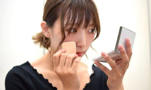 手鏡を見ながら真剣に化粧下地を塗る女性
