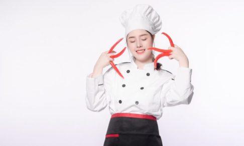 赤トウガラシを何本も持ってポーズを決めている女シェフ
