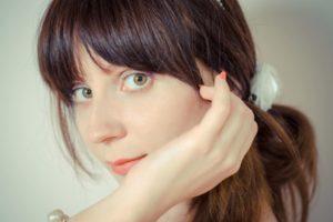 髪を一つに結んでコーラルのネイルを付けている女性の45度のアップ