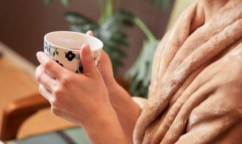 暖かそうなガウンを着て温かい飲み物を持っている手元