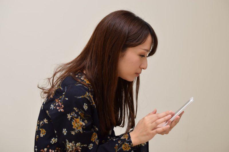 スマホを操作しながら猫背になっている日本人女性