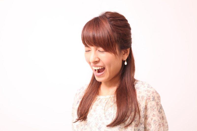 一生懸命口を開けて声を出している日本人女性