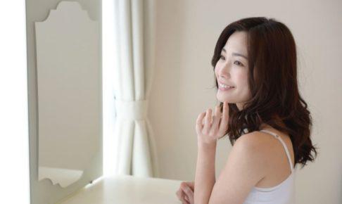 鏡をみてにっこり微笑む女性