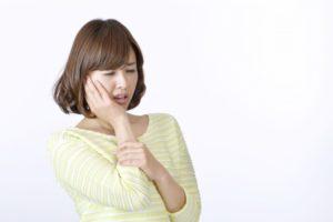 歯が痛くて押さえながら顔を歪ませている女性
