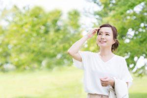 木々が生い茂る公園のなかで白色のカットソーを着た女性が額に手を当てている