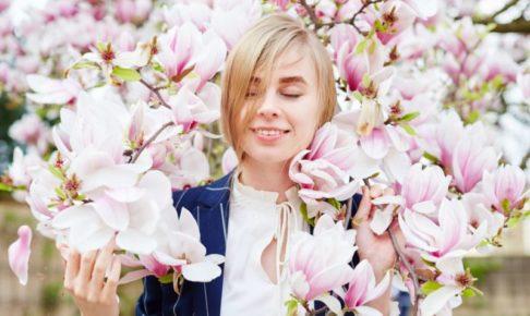淡い木蓮の花に囲まれてうっとりしている外国人女性
