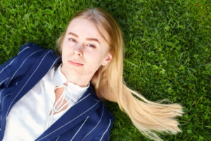 芝生に寝そべってキリッとした表情を見せる女の子