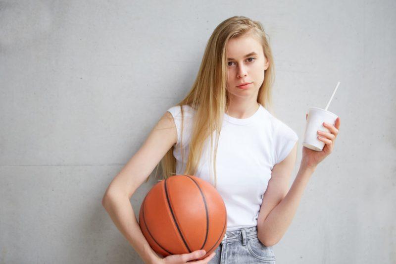 ジュースを持ってバスケットをしようとしている女子