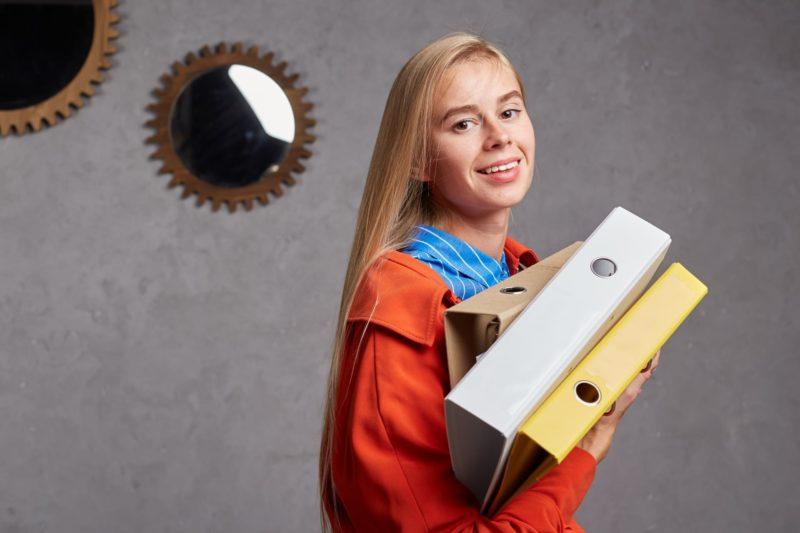 オレンジの上着を着て仕事に没頭している20代女性