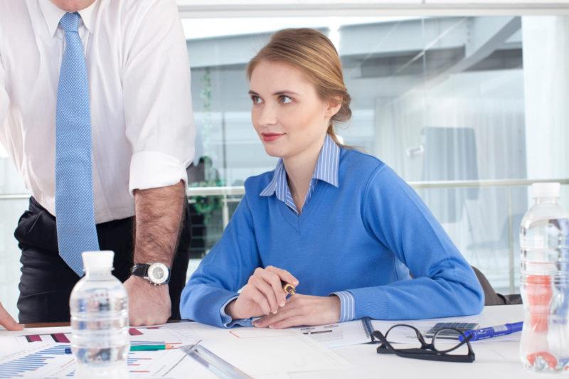 青いセーターとシャツでバリバリ仕事をしている30代女性