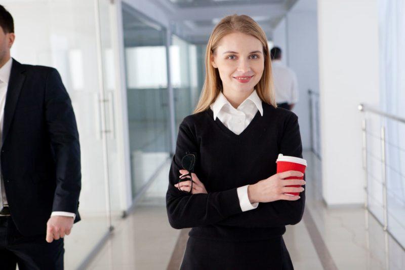 黒いセーターと白シャツでかっこよく仕事している40代女性