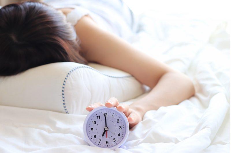 布団に寝て目覚まし時計に手を置く女性