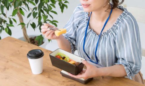 自分で作ったお弁当を食べる青いブラウスの女性