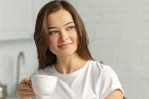 白いカップを持ってリラックスしている女性のアップ