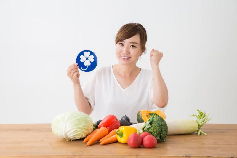 たくさんの野菜が置かれててこれから調理しようとやる気を出している女性