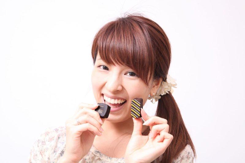 チョコレートを食べるのに満面の笑みを見せている女性