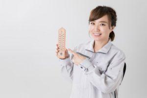 作業着を着て温度を計っている女性