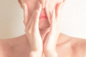 鼻を両手で押さえる女性