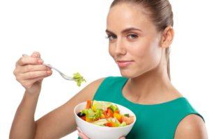 サラダボウルを食べる緑の服の白人女性