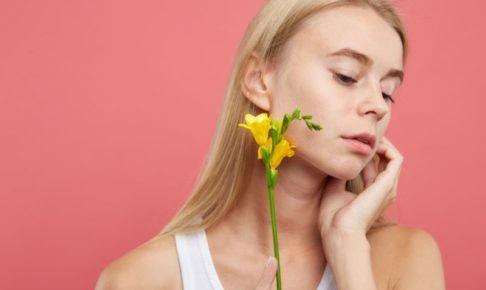 ピンクの背景に黄色い花を持って横を向いている女の子